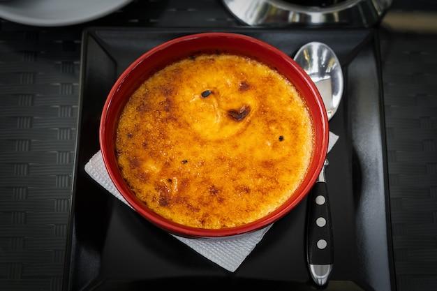 Köstliche braune karamellisierte crème brûlée in roter schüssel.