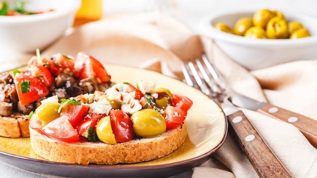 Köstliche bruschetta mit tomaten und champignons und bruschetta mit blauschimmelkäse, oliven und tomaten