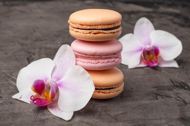 Köstliche bunte kekse macarons nahe orchideenblume als dekoration