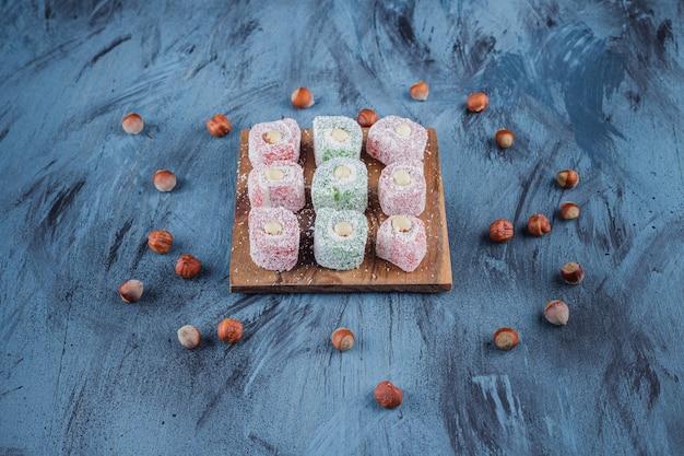Köstliche bunte süße köstlichkeiten mit nüssen auf holzbrett.