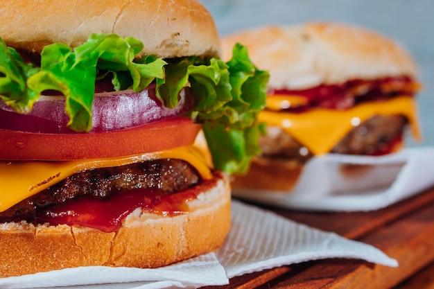 Köstliche burger mit speck und cheddar-käse und mit salat, tomate und roten zwiebeln und speck auf hausgemachtem brot und ketchup auf einer holzoberfläche und rustikalem hintergrund. fokus im ersten burger.