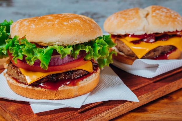 Köstliche burger mit speck und cheddar-käse und mit salat, tomate und roten zwiebeln und speck und cheddar auf hausgemachtem brot mit samen und ketchup auf einer holzoberfläche und rustikalem hintergrund.