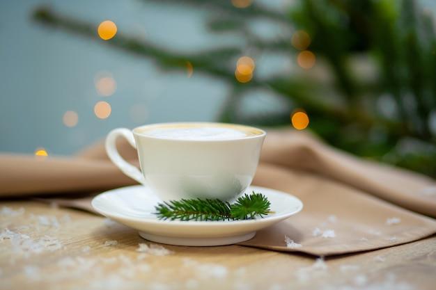 Köstliche cappuccinokaffeetasse, leuchtkäfer und fichtenzweige.