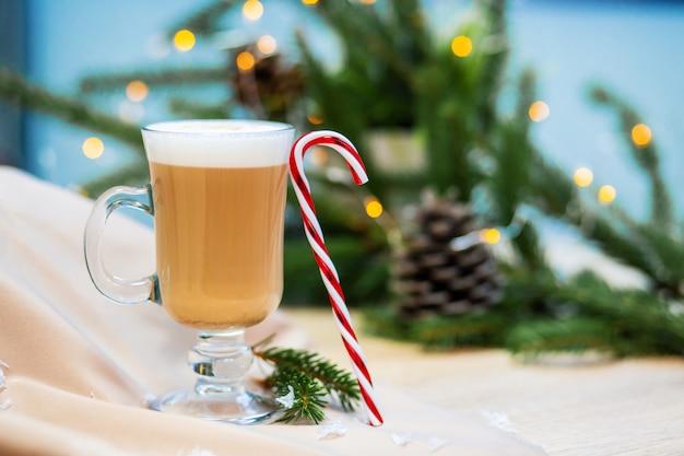 Köstliche cappuccinokaffeetasse und weihnachtssüßigkeitsbonbon. glühwürmchen und fichte zweige hintergrund.