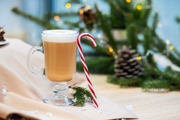 Köstliche cappuccinokaffeetasse und weihnachtssüßigkeitsbonbon.