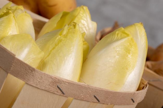 Köstliche chicorée-endivien aus frankreich oder belgien in einem kleinen holzkorb