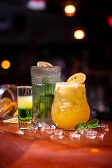 Köstliche cocktails des kalten sommers mit limette, minze und eis in einem glas mit tropfen. buntes alkoholisches cocktailgetränk an der bar.