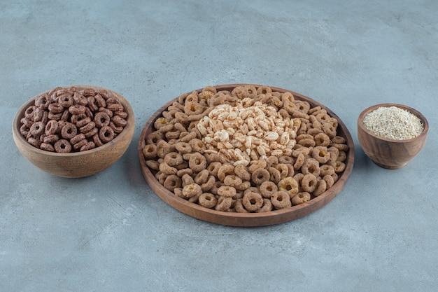 Köstliche cornflakes in den holzschalen, auf blauem hintergrund. foto in hoher qualität