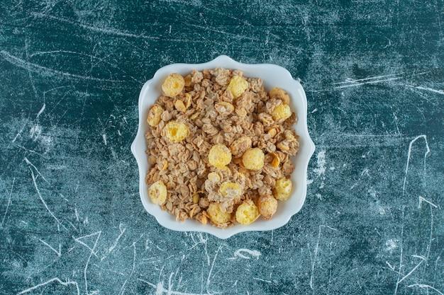 Köstliche cornflakes in einer schüssel auf blauem hintergrund. foto in hoher qualität