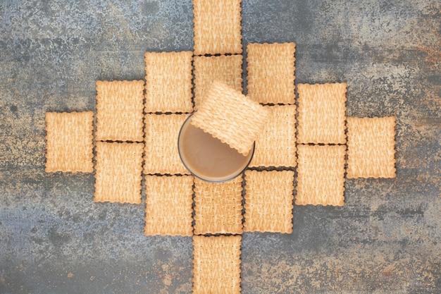 Köstliche cracker mit tasse kaffee auf marmorhintergrund. hochwertiges foto