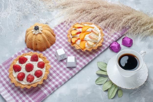 Köstliche cremige kuchen mit geschnittenen früchten zusammen mit pralinen und tee auf hellem schreibtisch, kuchenkeks süße sahne backen teezucker