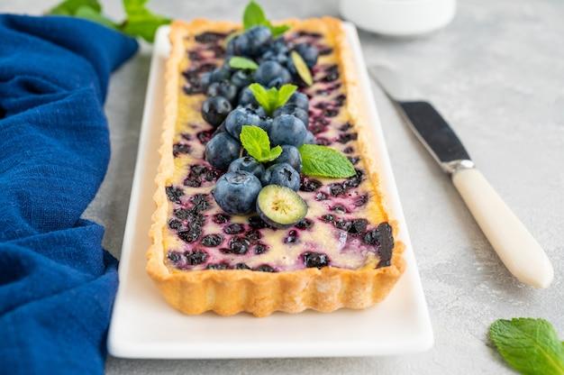Köstliche dessert-heidelbeertorte mit frischen beeren und vanillepudding sweet pie