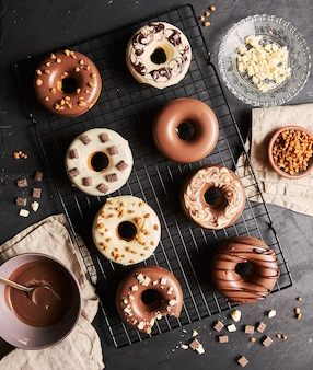 Köstliche donuts bedeckt mit der weißen und braunen schokoladenglasur mit den zutaten auf einem tisch