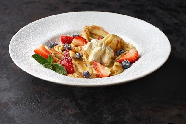 Köstliche dünne pfannkuchen mit erdbeeren, hüttenkäse und honig auf schwarzem tisch