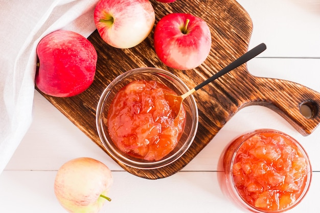 Köstliche duftende marmelade von reifen herbstäpfeln in einem glas und in einer schüssel. ansicht von oben.