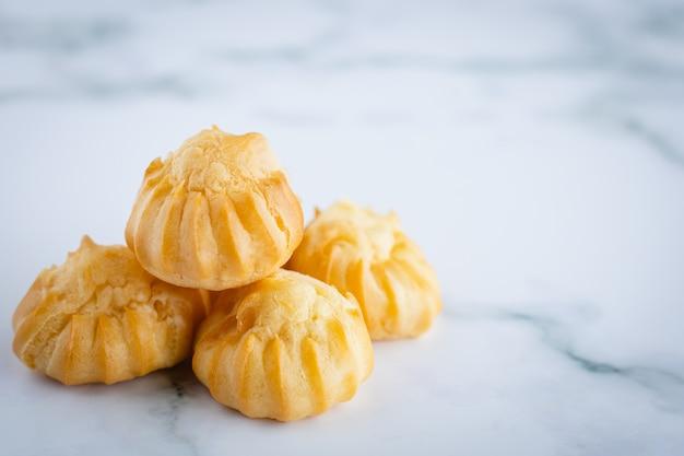 Köstliche eclair-vanillecreme, choux-teig, gefüllt mit einer sahne, hausgemachte bäckerei auf weißem marmorhintergrund für snackessen-konzept