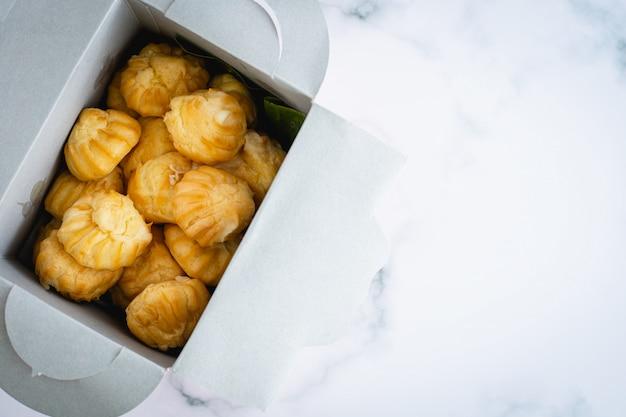 Köstliche eclair-vanillecreme, choux-teig, gefüllt mit einer sahne, hausgemachte bäckerei in der papierboxverpackung auf weißem marmorhintergrund für snack-ess-konzept