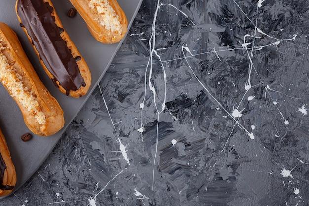 Köstliche eclairs aus süßer schokolade und vanille auf dunklem schneidebrett.