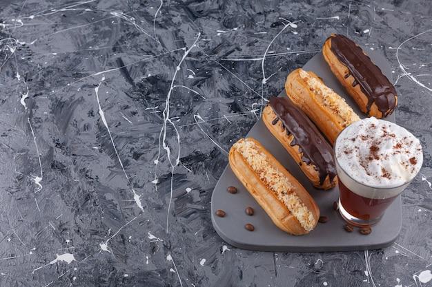 Köstliche eclairs aus süßer schokolade und vanille und mit einer tasse kaffee auf einem dunklen schneidebrett.