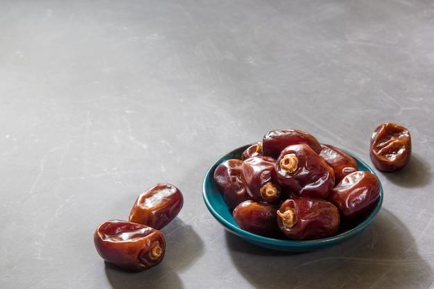 Köstliche entsteinte daten an der grauen tabelle. ramadan, iftar food-konzept. kopieren sie platz.