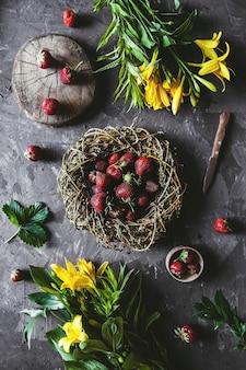 Köstliche erdbeeren mit gelben blumen auf einem dunkelgrauen hintergrund in einem weinlesekranz. gesundes essen, obst