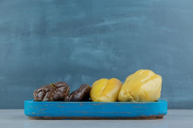 Köstliche essiggurken auberginen und paprika auf dem holzteller