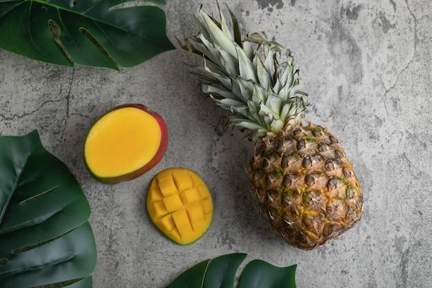 Köstliche exotische mangofrucht und ananas auf marmoroberfläche.