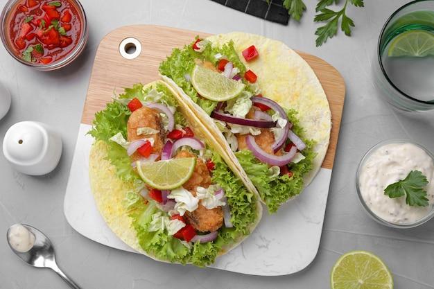 Köstliche fisch-tacos auf hellgrauem tisch serviert, flach