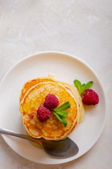 Köstliche flauschige goldene pfannkuchen in einem teller auf weißem marmorhintergrund