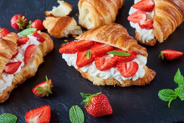 Köstliche französische croissant-sandwiches mit frischen reifen erdbeeren und schlagsahne auf einem steintablett auf einem schwarzen holztisch