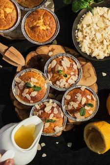Köstliche frisch gebackene zitronenmuffins mit mandelflocken mit zuckerguss, draufsicht