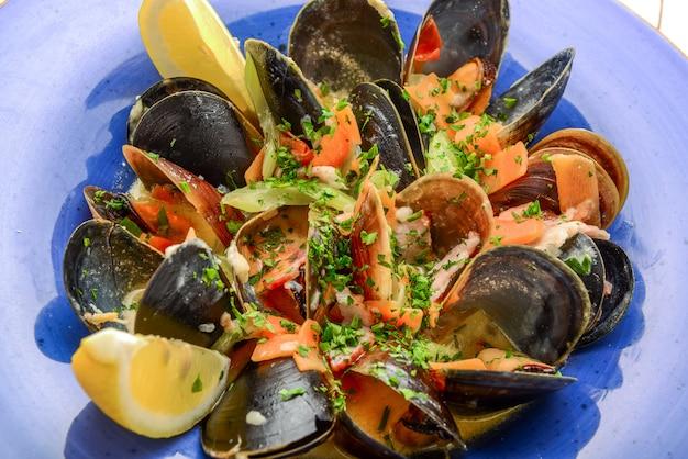 Köstliche frisch gekochte schwarze miesmuscheln in der tomatensauce in einer weinlesekasserolle mit löffel nahe bei zitronenscheibe auf einem hölzernen hintergrund