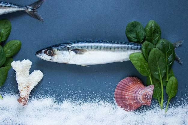 Köstliche frische fische auf blauem hintergrund. fisch mit aromatischen kräutern, zwiebeln, fisch im wasser schwimmen konzept