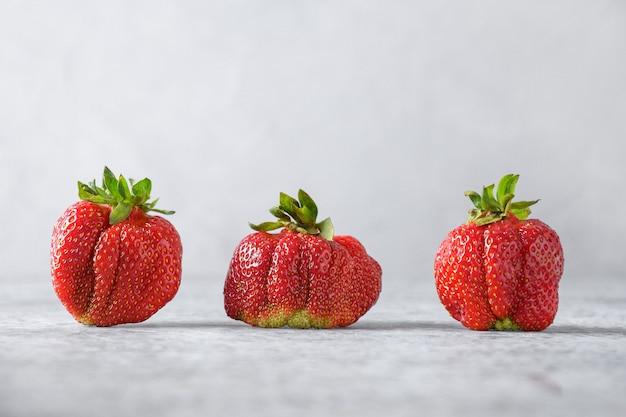 Köstliche frische hässliche erdbeerkonzept bio-öko-produkte Premium Fotos