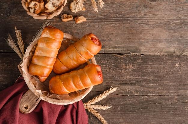 Köstliche frische kulinarische backwaren - würstchen im teig mit kopienraum auf hölzernem hintergrund