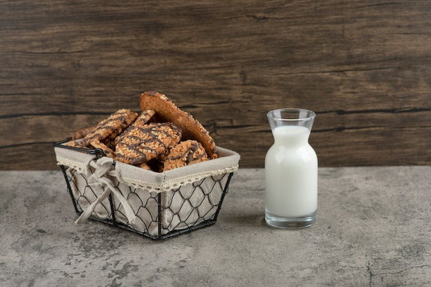 Köstliche frische mehrkornplätzchen mit schokoladenglasur im korb mit einem glas milch.