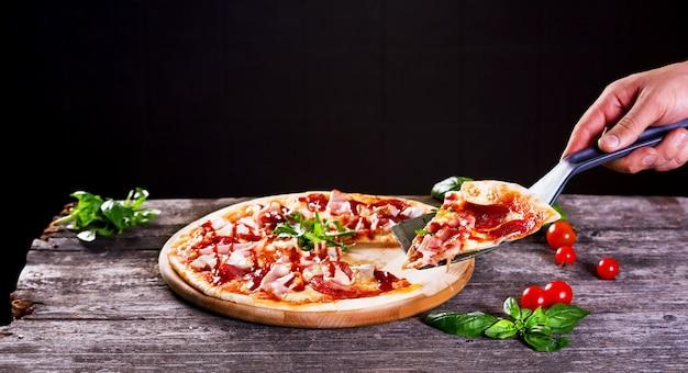 Köstliche frische pizza mit speck und tomatenmark auf dem hölzernen hintergrund. ansicht von oben.