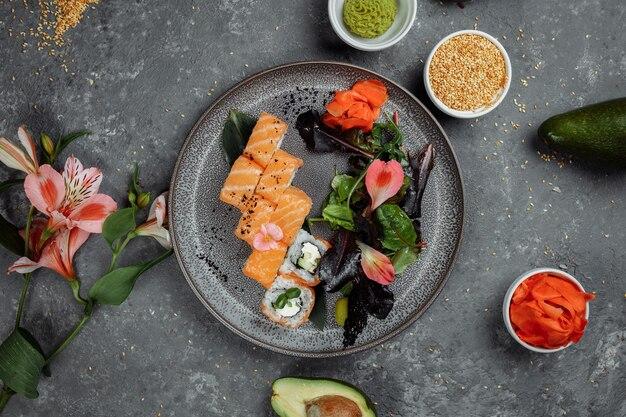 Köstliche frische sushi-rollen mit lachs und philadelphia-käse auf grauem teller. traditionelle japanische meeresfrüchte, gesundes lebensmittelkonzept.