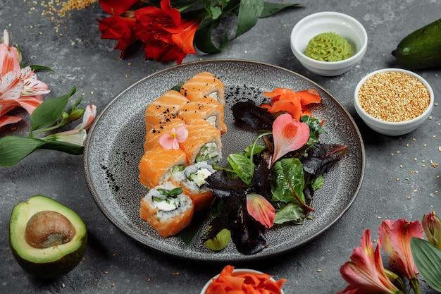Köstliche frische sushi-rollen mit lachs und philadelphia-käse auf grauem teller