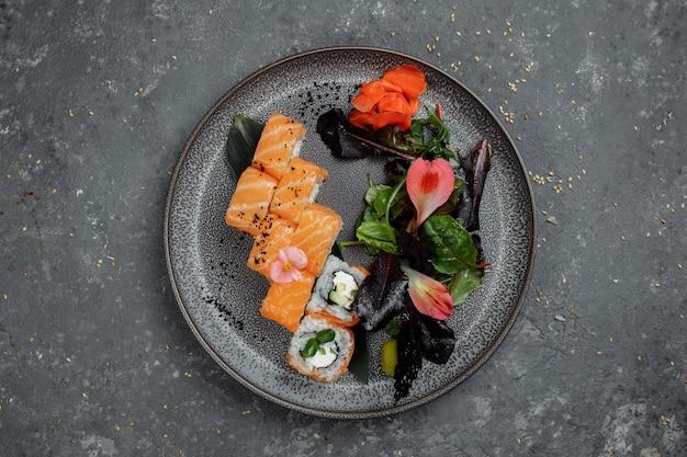 Köstliche frische sushirollen mit lachs und philadelphia-käse auf grauer platte auf dunklem steinhintergrund. traditionelle japanische meeresfrüchte, gesundes lebensmittelkonzept