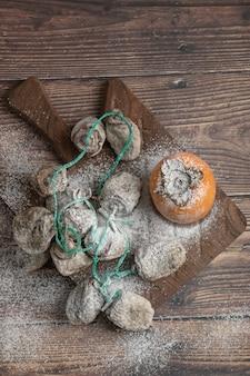 Köstliche frische und getrocknete kakifrüchte auf holzbrett
