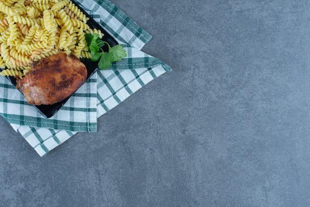 Köstliche fusilli mit hühnchen auf dunklem teller.