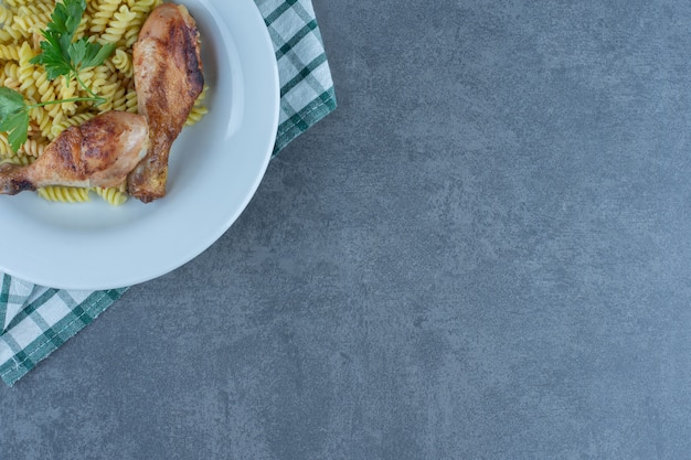 Köstliche fusilli mit hühnerbeinen auf weißem teller.