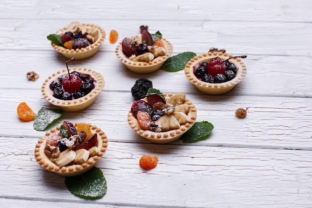 Köstliche gebackene fruchtkörbe mit beeren, exotischen früchten, grün und nüssen