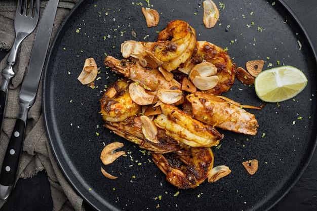 Köstliche gebratene garnelen mit knoblauch, curry und mangosauce, auf teller, auf schwarzem tisch, draufsicht flach