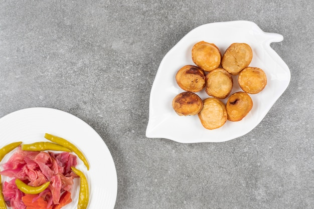 Köstliche gebratene knödel auf weißem teller mit gurken