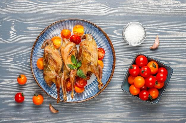 Köstliche gebratene wachteln mit kräutern und kirschtomaten.