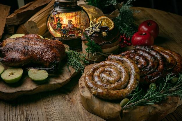 Köstliche gebratene weihnachtsente mit äpfeln, hausgemachter wurst und weihnachtskuchen