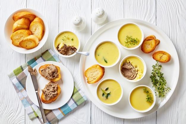 Köstliche geflügelleberpastete mit kräutern und butter in auflaufförmchen auf einer platte mit gerösteten scheiben baguette und pastetenleber-sandwiches