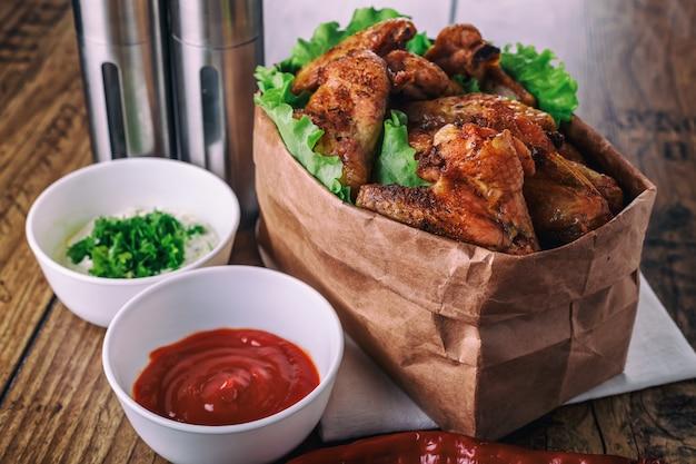 Köstliche gegrillte hühnerflügel mit knoblauch- und tomatensauce mit kopfsalat in der lebensmittelpapiertüte